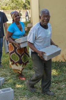 mensen in het dorp helpen mee aan de bouw van een nieuw leslokaal